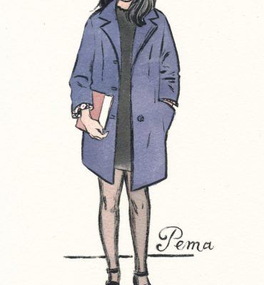 young lady holding a book dressed in a well-cut navy blue coat